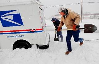 Russell Henderson noticed postal worker George Staros needed some help getting out of a snow drift on Douglas Blvd. near SE 15th Street. Henderson attached a chain from his truck to the mail truck and then helped dig snow from beneath the tires of Staros' vehicle. Within ten minutes, the two men had freed the vehicle and Staros continued with his mail delivery duties. Winter storm creates whiteout conditions and caused snow drifts that made problems for the few motorists who ventured out Tuesday morning, Feb. 1, 2011. Photo by Jim Beckel