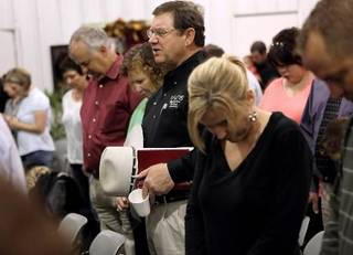 """Surrounded by visitors and members of Ridgecrest Baptist Church, Jim Brunk (center) leads the congregation in prayer during """"Surthrivor Service"""" at Ridgecrest Baptist Church in Bridge Creek Oklahoma on May 3, 2009. Photo by John Clanton"""