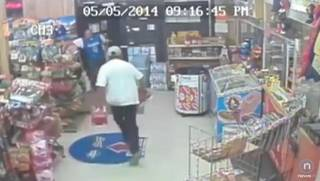 In this screen grab from a security video released by Oklahoma City police, one man holds up the Super Mart at 532 S 15 while the other runs out with two 30-packs of Budweiser beer.