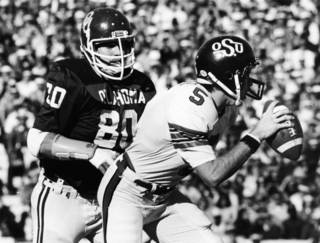 BEDLAM: University of Oklahoma defenseman Rick Bryan (80) closes in on Oklahoma State University quarterback John Doerner (5) during game action in Norman. The Sooners smothered the Cowboys, 63-14. Staff photo by Jim Argo taken 11/29/80. File: College Football/OU/OU-OSU/Rick Bryan/1980