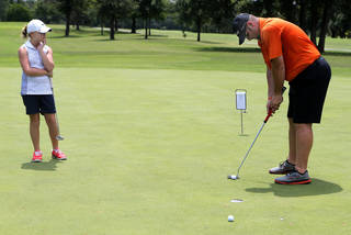 Maddi Kamas watches her father, Laremy, putt during the 11th annual parent-child tournament at KickingBird Golf Course in Edmond. PHOTO BY SARAH PHIPPS, THE OKLAHOMAN SARAH PHIPPS -
