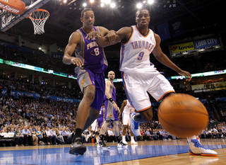 Oklahoma City Thunder power forward Serge Ibaka (9) and Phoenix Suns center Channing Frye (8) go after a loose ball during the NBA basketball game between the Oklahoma City Thunder and the Phoenix Suns at the Chesapeake Energy Arena on Wednesday, March 7, 2012 in Oklahoma City, Okla. Photo by Chris Landsberger, The Oklahoman