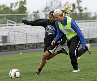 Tayler Shoopman, left, tries to get the ball past Ashley Garver during soccer practice at Piedmont High School in Piedmont, Okla., Wednesday, April 11, 2012. Photo by Nate Billings, The Oklahoman