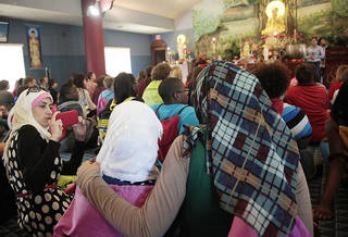 Hind Khader takes a picture of Sireene Khader, middle, and Amna Amir during the Oklahoma Council of Churches' sixth annual Interfaith Youth Tour Sunday at the Vien-Giac Buddhist Temple in Oklahoma City . Photo by SARAH PHIPPS, The Oklahoman