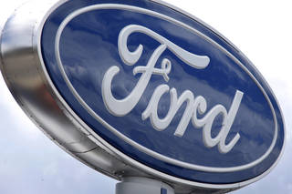 Clouds are reflected in the Ford sign at a dealership in Wexford, Pa. AP Photo Keith Srakocic