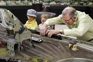 Jimmy Samis demonstrates his train collection to his great-grandchildren Sam Kirkpatrick, 3, and 16-month-old Thomas Fellers, at his home in Nichols Hills on Oct. 28. Photo by Paul Hellstern, The Oklahoman PAUL HELLSTERN
