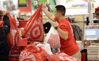 A Target employee hands bags to a customer at the register at a Target store in Colma, Calif. Target's fiscal fourth-quarter net income dipped 2 percent as it dealt with intense competition during the crucial holiday season. AP Photo Jeff Chiu