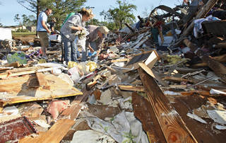 Jessica Eldridge, center, and her grandfather, Ernest Eldridge, right, salvage belongings from what is left of Jessica's home in Tushka, Okla., Friday, April 15, 2011, after it was blown onto a road and collided with another home during an overnight tornado. (AP Photo/Sue Ogrocki)