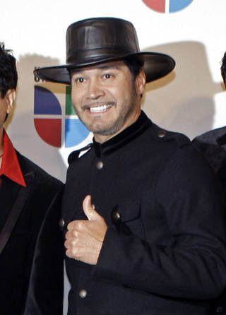 """This Nov. 13, 2008 file photo shows Oscar De La Rosa, lead singer for the Tejano group La Mafia, at the 9th annual Latin Grammy Awards in Houston. De La Rosa was knocked unconscious by a man in an unprovoked attack outside a Houston club on Monday, May 13, 2013. De La Rosa has facial cuts, eye damage and he lost two teeth. La Mafia is considering whether to cancel any performances. The band, which formed in 1980 in Houston, won a Grammy in 2006 for the album, """"Nuevamente."""" (AP Photo/LM Otero, file)"""