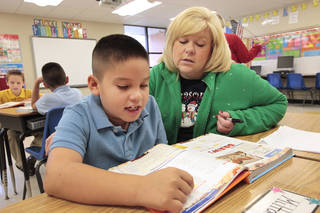 Pierce Elementary Principal Paula Pluess, right, helps third-grader Milton Celaya with a reading assignment, Wednesday, December, 4, 2013. Photo by David McDaniel, The Oklahoman