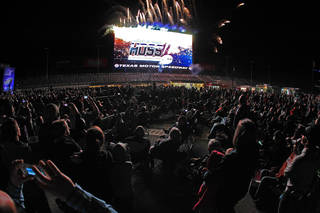 Fireworks light up near a high-definition video board that was unveiled Wednesday, March 19, 2014, at Texas Motor Speedway in Fort Worth, Texas. The screen is 218 feet wide and about 95 feet high. It is about 125 feet above ground level in the middle of the backstretch at the 1 1/2-mile track. (AP Photo/Fort Worth Star Telegram, Paul Moseley) MAGS OUT (FORT WORTH WEEKLY, 360 WEST); INTERNET OUT