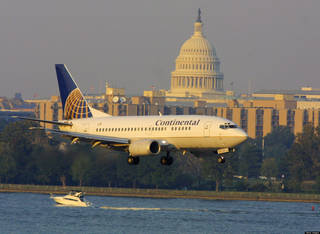 395437 01: With the U.S. Capitol in the background a Continental Airlines Boeing 737 comes in to land at Washington's Reagan National Airport October 5, 2001 in Washington DC. With unprecedented security the airport was trying to get back to normal after it reopened yesterday and became the last commercial airport in the U.S. to reopen since the September 11 attacks. (Photo by Joe Raedle/Getty Images)
