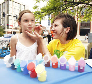 Sara Jacobson paints the face of Allie Morris, 9, Saturday during the Norman Music Festival on Main Street. Photo by STEVE SISNEY,THE OKLAHOMAN