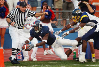 Kansas running back John Randle (1) dives for a touchdown past Toledo free safety Patrick Body (11) during the first quarter in Lawrence, Kan., Saturday, Sept. 11, 2004. Side judge Jeff Ulery, left, is in position for the call. Randle took an Adam Barmann pass 55 yards for the score. (AP Photo/Orlin Wagner) ORLIN WAGNER - ASSOCIATED PRESS