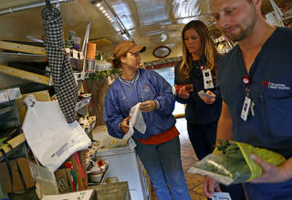 Paulette Rink helps customers Jodi Meacham and Jeremy Beller inside a 1985 school bus that is used as a farmers market while parked Thursday outside Oklahoma Heart Hospital. Photos by Bryan Terry, The Oklahoman