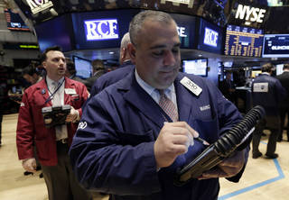 Trader Mario Innella, center, works on the floor of the New York Stock Exchange Thursday, March 13, 2014. Stocks opened higher as traders were encouraged by a pickup in retail sales and more signs of health in the U.S. job market. (AP Photo/Richard Drew)