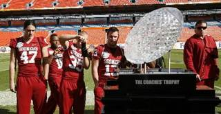 Oklahoma players take pictures of the BCS Championship trophy during media day at Dolphin Stadium in Miami on Monday Jan. 5, 2009. (AP Photo/J. Pat Carter)