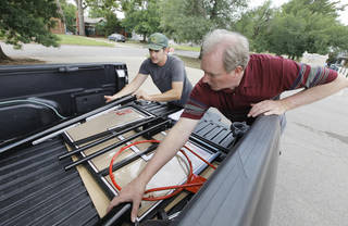 J. J. Gourley, Westminster Presbyterian Church deacon, and Lee Cosby, Eagle Ridge community relations, unload parts to begin putting together a basketball goal donated to a family raising foster children. Photos by Paul B. Southerland, The Oklahoman PAUL B. SOUTHERLAND - PAUL B. SOUTHERLAND