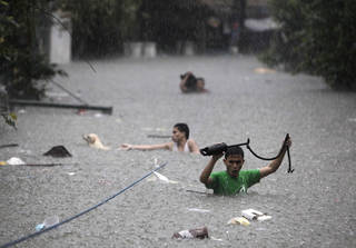 Men crosses deep floodwaters in San Juan, north of Manila, Philippines, on Wednesday Aug. 8, 2012. Widespread flooding paralyzed the Philippine capital and many other areas on Wednesday as rescue efforts focused on the large number of distressed residents who are still marooned on their roof tops and unable to move to high ground. (AP Photo/John Javellana) ORG XMIT: XAF131