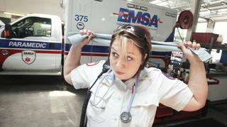 EMSA paramedic Tori Spencer ties a cooling towel around her neck Tuesday in Oklahoma City. EMSA issued the cooling towels to staff members to help them stay cool during the heat wave. Photo by Paul B. Southerland, The Oklahoman