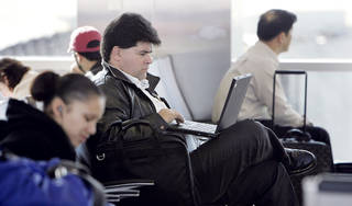 Traveler Ken Yonich works on his laptop at Will Rogers World Airport. Oklahoma Archives Photo
