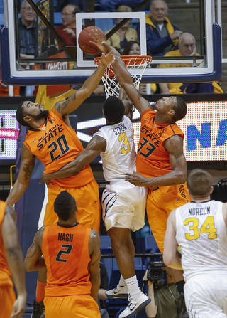 Oklahoma State's Marcus Smart (33) and Michael Cobbins (20) block the shot of West Virginia's Juwan Staten (3) during the second half of an NCAA college basketball game in Morgantown, W.Va., on Saturday, Feb. 23, 2013. Oklahoma State defeated West Virginia 73-57.(AP Photo/David Smith) ORG XMIT: WVDS114