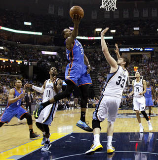 Oklahoma City's Kevin Durant (35) tries to score between Memphis' Mike Conley (11) and Memphis' Marc Gasol (33) during Game 3 in the first round of the NBA playoffs between the Oklahoma City Thunder and the Memphis Grizzlies at FedExForum in Memphis, Tenn., Thursday, April 24, 2014. Photo by Bryan Terry, The Oklahoman
