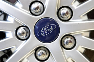 This 2013 file photo shows a Ford emblem on a wheel of a sedan at a Ford dealership in Norwood, Mass. May Sales from the major automakers were reported Tuesday. AP Photo Steven Senne - AP