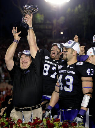 This Jan. 1, 2011 file photo shows TCU head coach Gary Patterson holding up the Rose Bowl Trophy after defeating Wisconsin in the Rose Bowl NCAA college football game, in Pasadena, Calif. People with knowledge of the decision say Big 12 leaders have agreed to invite TCU to join the fractured league as early as the 2012 football season. The offer to TCU will be extended sometime in the next few days, according to two people with ties to the Big 12. The people spoke only on condition of anonymity because the league has not announced the decision. (AP Photo/Mark J. Terrill, File)