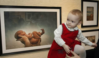 Brandy McDonnell's 21-month-old daughter Brenna is shown on March 21 with the photograph of her as a newborn taken by M.J. Alexander and exhibited at the Capitol's North Gallery. Photo By David McDaniel/The Oklahoman David McDaniel - The Oklahoman