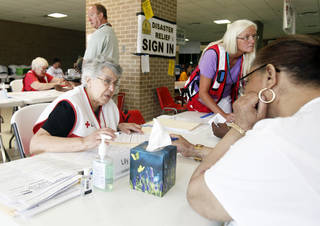 Red Cross volunteers Lily Boutros, left, of Massachusetts, and Tina Spencer, of Utah, work Wednesday with tornado victims on required relief paperwork at Westmoore High School. Photo by Aliki Dyer, The Oklahoman. Aliki Dyer