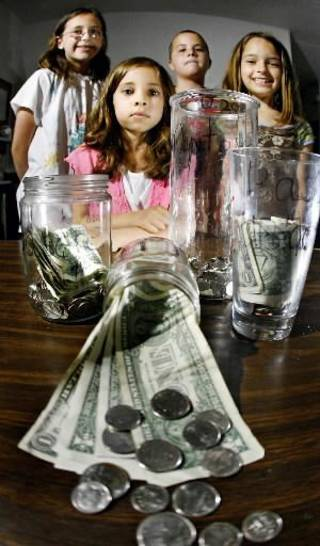 Dillard, 9, (from left) show the money they've saved for a family reunion trip using their money jars.