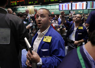 Trader Peter Iocolano, center, works in the oil options pit at the New York Mercantile Exchange, Wednesday, July 3, 2013. Oil climbed above $101 a barrel as the political crisis in Egypt intensified. (AP Photo/Richard Drew) ORG XMIT: NYRD103