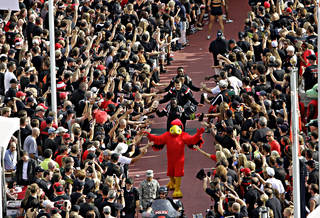 The Cardinal mascot leads the Louisville football team in a pregame march before the Louisville-Miami game Monday night. (AP Photo)