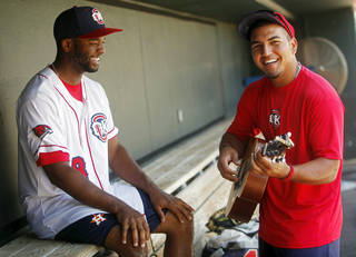 Redhawks outfielder Austin Wates laughs while teammate Carlos Perez plays his guitar in the dugout before practice at the Chickasaw Bricktown Ballpark in Oklahoma City on July 8, 2014. Photo by KT King/The Oklahoman