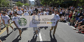 Workers carry a Starbucks banner during the gay pride parade in Salt Lake City. Rick Bowmer -
