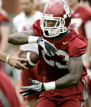 Brandon Williams takes a handoff from Blake Bell during the first day of spring practice at the University of Oklahoma in Norman on Monday, March 21, 2011. Photo by John Clanton, The Oklahoman