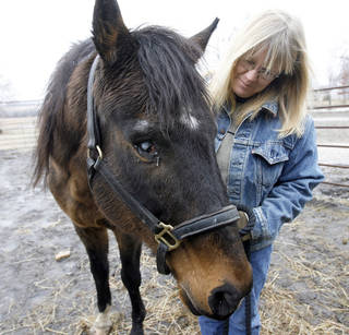 Kristin Chambers, executive director of the Winding Road Equine Rescue & Retirement, poses for a picture with Clever Allemont on Tuesday in Williamsburg, Kan. AP Photo