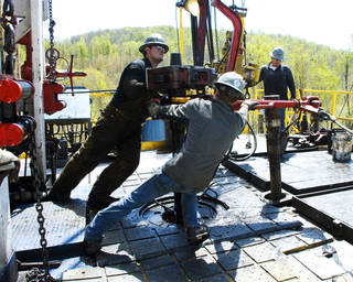 In this April 23, 2010 photo, workers move a section of well casing into place at a Chesapeake Energy natural gas well site near Burlington, Pa. (AP Photo/Ralph Wilson)
