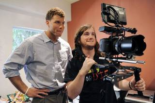 Los Angeles Clippers basketball player Blake Griffin, left, watches a take on the monitor of camera operator Brian Lane during the first day of Griffin's week-long internship at comedy video website Funny Or Die, Tuesday, Aug. 23, 2011, in Los Angeles. A fan of Funny Or Die and comedy in general, Blake will spend the week on tasks ranging from running office errands to helping out on productions. (AP Photo/Chris Pizzello) ORG XMIT: CACP106