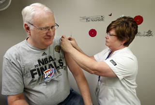 George Henschel gets a flu shot from nurse D.J. Gentry at the Cleveland County Health Department. PHOTO BY STEVE SISNEY, THE OKLAHOMAN STEVE SISNEY
