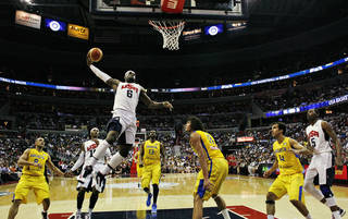 Team USA forward LeBron James goes up for a dunk in front of Brazil forward Anderson Varejao (11) during the first half of an Olympic men's exhibition basketball game, Monday, July 16, 2012, in Washington. USA won 80-69. (AP Photo/Alex Brandon) ORG XMIT: VZN130