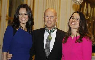 American movie star Bruce Willis , poses for the press with his wife model Emma Heming, left, after being awarded with the medal of Commander of Arts and Letters by French culture minister Aurelie Filippetti, right, in Paris, Monday Feb. 11, 2013.(AP Photo/Remy de la Mauviniere)