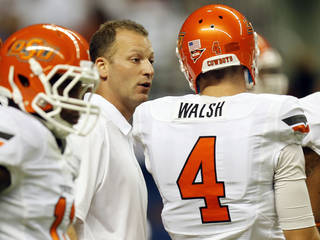 OSU offensive coordinator Mike Yurcich talk to quarterback J.W. Walsh (4) as the Cowboys warm up before a college football game between the University of Texas at San Antonio Roadrunners (UTSA) and the Oklahoma State University Cowboys (OSU) at the Alamodome in San Antonio, Saturday, Sept. 7, 2013. Photo by Nate Billings, The Oklahoman