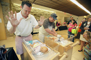 """Jason Davey, left, won the diaper-changing contest for expectant dads at Integris Health Edmond during a """"Babies, Bottles and Booties"""" event. Cory Reginger, right, was among the five men who competed. His winning time was 27 seconds. The next closest time was 31 seconds. Davey walked away with a $25 gift card from the Meat House in Edmond. PHOTOS BY PAUL HELLSTERN, THE OKLAHOMAN"""