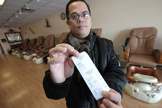 Kent Phan, owner of K&V Nail Spa, holds a receipt for $30, the entire income on Jan. 27. A road construction project, that is finally finished, has been hurting the businesses at the intersection of 164 St. and Pennsylvania Ave., including K&V Nail Spa. David McDaniel - The Oklahoman