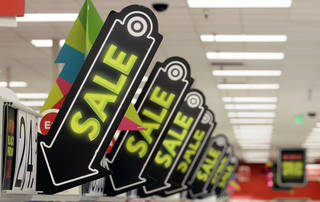 Sale signs are displayed at a Target store in Colma, Calif. Big retailers, from Best Buy to Target to Toys R Us, are engaging in a price war this holiday season, and shoppers can score some good deals if they know how to navigate them. But what's different this holiday season is that Best Buy and Target are matching online retailers such as Amazon.com for the first time. That's a big deal, since online prices tend to be lower than those in the store. AP Photo Jeff Chiu