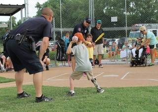 Yukon police department members provide guidance as kids participate in the Yukon Spirit Baseball League. The league for special needs children has wrapped up its season. The league is sponsored by the Yukon police and fire departments and the parks and recreation department. PHOTO PROVIDED PROVIDED