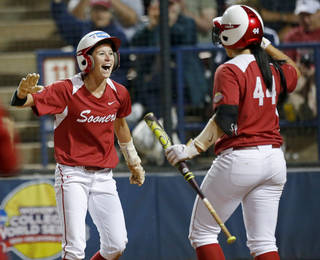 Oklahoma's Brianna Turang, left, celebrates with Lauren Chamberlain after scoring in the third inning against Washington during a Women's College World Series softball game at ASA Hall of Fame Stadium in Oklahoma City, Sunday, June, 2, 2013. Photo by Sarah Phipps, The Oklahoman Download