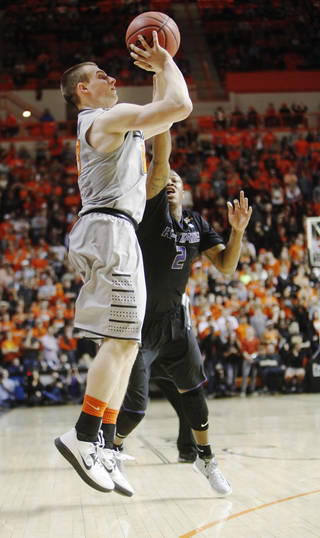 Oklahoma State's Phil Forte (13) shoots a jump shot while Kansas State defender Marcus Foster (2) jumps to block the shot during an NCAA college basketball game between Oklahoma State University (OSU) and Kansas State held in Gallagher-Iba Arena in Stillwater, Okla., Monday, March 3, 2014. Oklahoma State defeated Kansas State 77-61. Photo by KT King/ For The Oklahoman